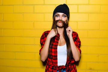 Beautiful young sexy hipster girl posing, smiling, do fake mustache near urban yellow wall background in red plaid shirt, shorts, hat.