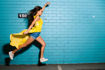 Beautiful young sexy hipster girl posing, smiling, superman flying near urban blue wall background in yellow dress, shorts, shirt, sneakers.