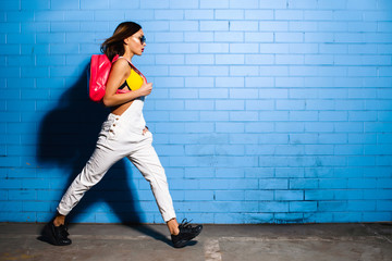 Beautiful young sexy hipster girl goes near urban blue wall background in yellow swimsuit, white jumpsuit, sneakers, sunglasses, pink backpack.