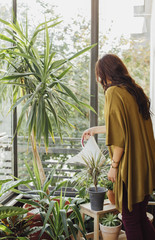 Caucasian woman watering potted plants