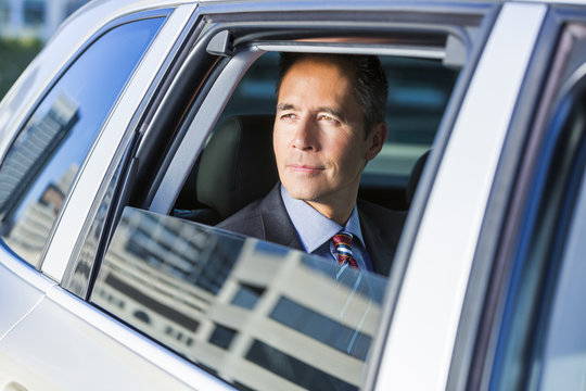 Mixed race businessman sitting in car