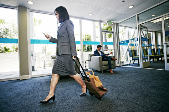 Japanese businesswoman rolling luggage in office