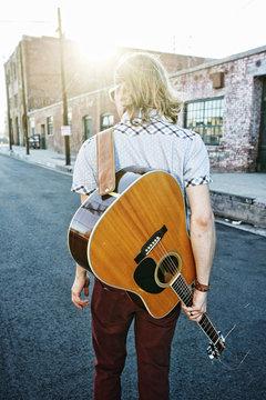 Caucasian man carrying guitar outdoors