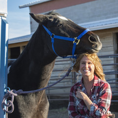 Caucasian woman smiling with horse on ranch
