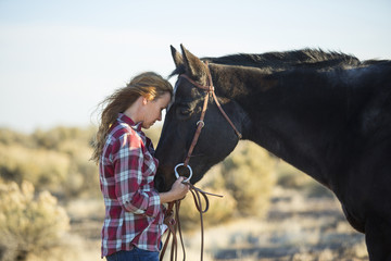 Caucasian woman hugging horse in field