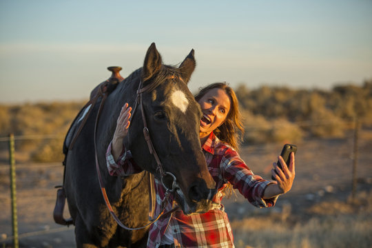 Caucasian woman taking selfie with horse