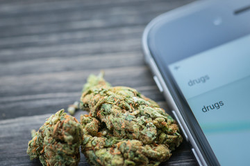 Phone and weed on a rustic wooden board