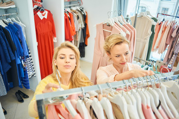 Two girls choosing a dress on a rack with hangers in a clothing store