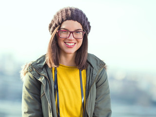 Portrait of beautiful smiling young woman wearing eyeglasses and hat walking in the city