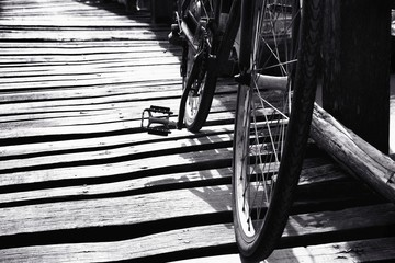 Black and white a bicycle on the wooden bridge