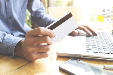 Man using laptop and mobile phone to online shopping and pay by credit card. Vintage tone, Retro filter effect, Soft focus, Low light.(selective focus)