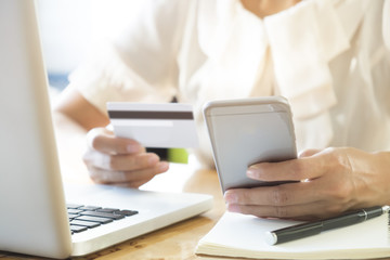 Woman holding mobile phone and credit card on laptop for online