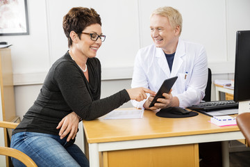 Happy Patient And Male Doctor Communicating Over Digital Tablet
