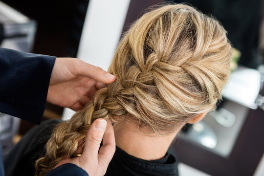 Closeup Of Hairstylist's Hands Braiding Client's Hair