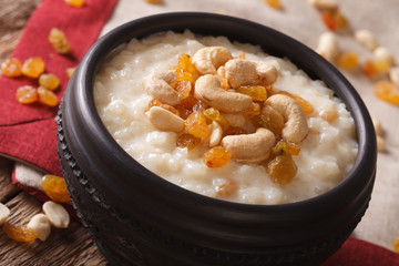 rice pudding with nuts and raisins in a bowl close-up. horizontal