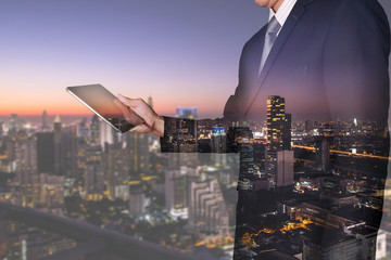Double exposure of businessman looking the tablet and airport as communication and transportation concept.