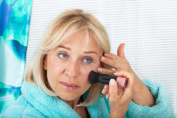 Middle aged woman applying her make-up with a big brush