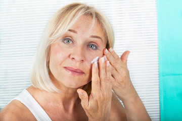 Woman in her 60s applying skin cream on her face. Anti-aging concept.