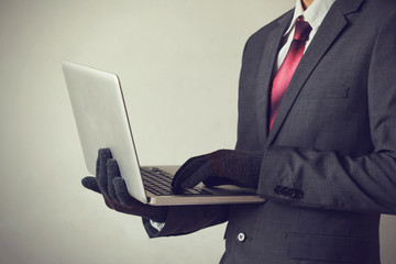 Business man wearing gloves and using computer - fraud, hacker, theft, cyber crime concept - fototapety na wymiar