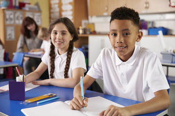 Two primary school pupils in classroom looking to camera