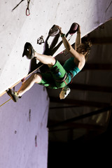 Female Climber on Overhanging Roof in night illumination