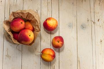 Несколько спелых нектарин в крафтовом пакете на деревянном фоне. Здоровое питание