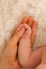 Father holding hand of a newborn baby in his palm