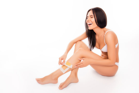 Attractive woman shaving her leg with wax stripe and feeling pai