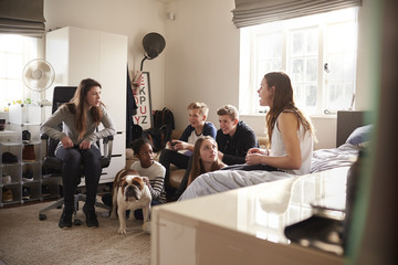 Group Of Teenagers Playing Video Game In Bedroom