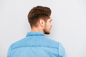 Rear view of young handsome man with bristle in blue shirt