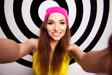 Beautiful girl with beaming smile in pink cap making selfie