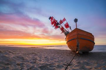 Zachód słońca nad morską plażą,kutry rybackie na piasku