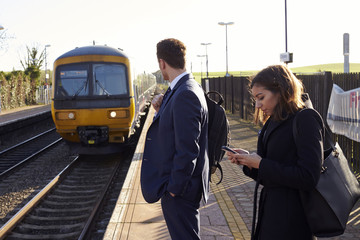 Commuters Waiting On Railway Platform Using Mobile Phones