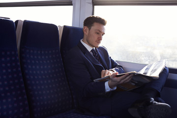 Businessman Commuting To Work Reading Newspaper On Train