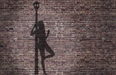 ombra di una prostituta appoggiata al lampione sul muro di mattoni
