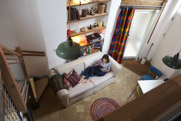 Woman Relaxing With Digital Tablet In Stylish Apartment