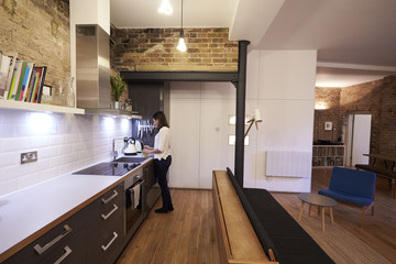 Woman Making Hot Drink In Kitchen Of Modern Apartment