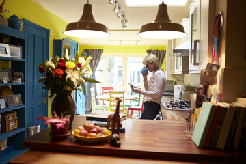 Woman Checking Messages On Mobile Phone In Kitchen