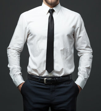 Midsection of young businessman in formal white shirt, black tie