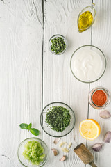 Natural yogurt and different seasoning on the white wooden table vertical