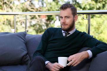 A handsome man in a shirt, tie and sweater sitting down outside on a summer day holding a mug. Relaxed and laid back.