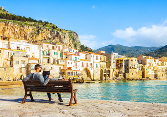 Couple sitting on bench, enjoying view of beach town of Cefalu in Sicily, Italy