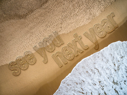 See You Next Year written on the beach