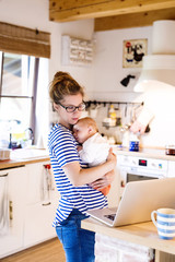 Mother with baby in kitchen looking at laptop
