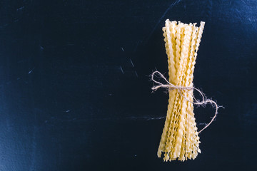Raw spaghetti on black wooden background, top view