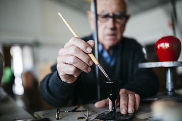 Senior man decorating ceramic in his spare time