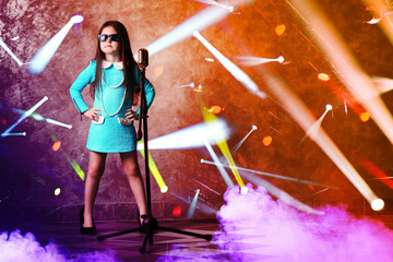 Beautiful super-star girl in dress with microphone and laser rays on brick wall background