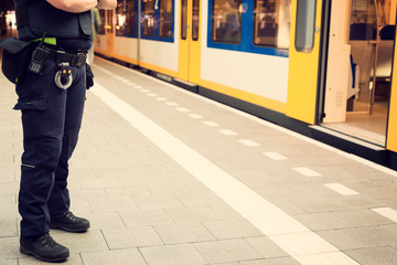Police officer guarding a train station to prevent terrorist attacks.