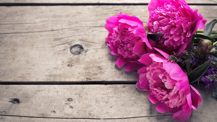 Bunch of pink peonies flowers on aged wooden background.