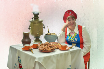 At an old samovar 3/Genre scene with an ethnic Russian woman in national dress near an old samovar...